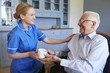 Nurse Giving Senior Man Cup Of Tea On Home Visit