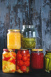 Variety glass jars of homemade pickled or fermented vegetables and jams in row with old dark blue wooden plank background. Seasonal preserves. - 180862991
