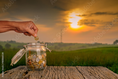 Papiers peints Morning Glory Hand putting coins in glass jar for saving money on old wood with blurred background.
