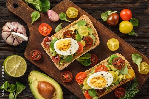 Fototapeta Bruschetta with avocado, egg and tomatoes.
