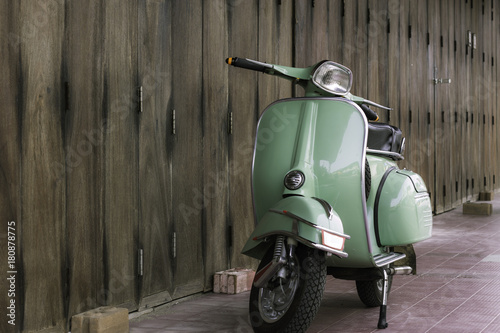 Fotobehang Scooter Green scooter against old house. wood wall mossy surface of building as background. Urban street in Thailand, Asia. Moped parked at moldy wood wall. Asian lifestyle and popular transport.