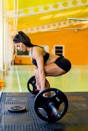 Poster Young pretty woman holding weights and doing fitness indoor