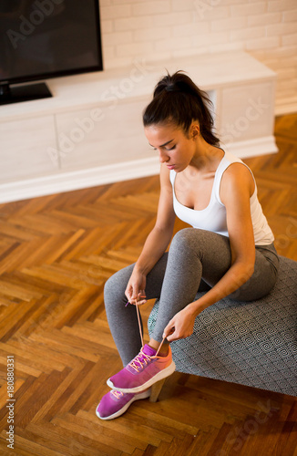 Fototapeta Young woman preparing for exercise at home