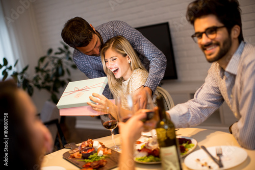Happy smiling young woman receives gift from young man for New Year or Christmas Poster
