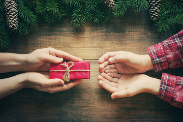 Red gift box in female hands and the child's hands accepting a gift, christmas fir tree on wooden background. Christmas celebration concept.