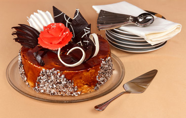 Luxurious cake with chocolate decorations on large platter, small saucers and spoons, on beige