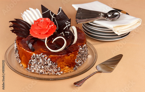 Poster Luxurious cake with chocolate decorations on large platter, small saucers and sp