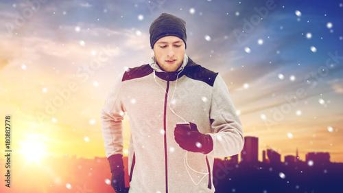 Deurstickers Jogging happy man with earphones and smartphone in winter