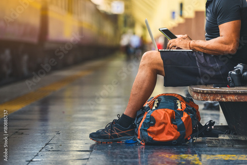 Fototapeta Digital nomad with backpack. Backpacker using a smart phone and a laptop at the train station