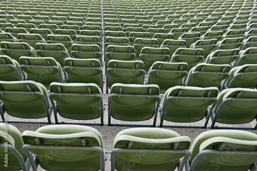 Sitzreihen grüner Plastikstühle in einem Stadion, von hinten gesehen