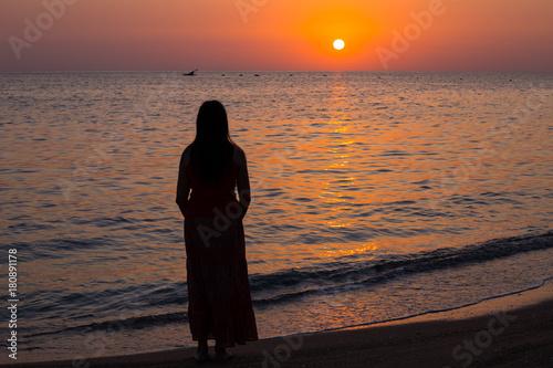 Papiers peints Orange eclat Girl and the sea. Sunrise on the sea coast