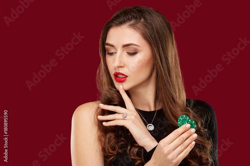 Pretty long hair woman in black dress holding chips for gambling плакат