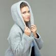Beautiful girl wearing gray coat with hood. Isolated portrait.