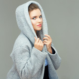Beautiful girl wearing gray coat with hood. Isolated portrait.