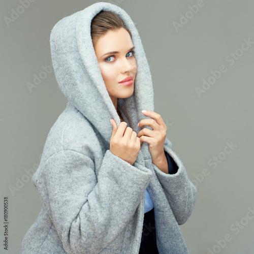 Plakat Beautiful girl wearing gray coat with hood. Isolated portrait.