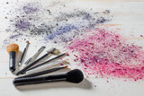 Beauty still life with makeup brushes and crushed eyeshadow colors - 180901511