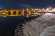 Long exposure of the old Devorgilla bridge and weir crossing the River Nith in Dumfries, southern Scotland at night. The bridge reflects off the calm waters above the thundering weir.