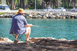 Retired senior man enjoys fishing from a pier into the river