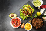 mexican tacos and ingredients like fried ground beef, tomato salsa, guacamole, corn and spices on a dark slate plate with copy space, top view from above, selected focus - 180917592