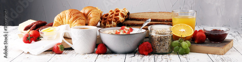 Wall mural Breakfast served with coffee, orange juice, croissants, cereals and fruits. Balanced diet