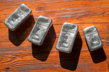 Molten silver bars on the background of mahogany.
