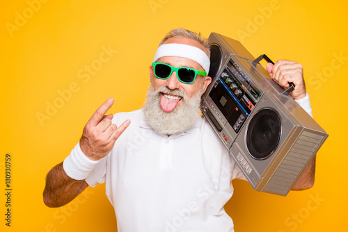 Cheerful excited aged funny active sexy athlete cool pensioner grandpa in eyewear with bass clipping ghetto blaster recorder. Old school, swag, sticking tongue, fooling, gym, workout, technology