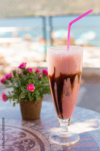 Foto op Plexiglas Milkshake Delicious milk dessert with chocolate and strаwberry on ceramic table and blurred background