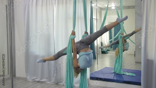 Wall mural Young woman is training in fabric hammock in studio. Female holds on to tissue loops with hands, hangs upside down and spreads legs wide. Beautiful blonde with tail, dressed in stylish sportswear
