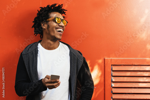 Foto Murales Afro young man using mobile phone.