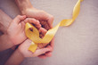 adult and child hands holding yellow gold ribbon, Sarcoma Awareness, Bone cancer, childhood cancer awareness