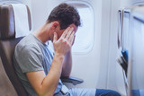 headache in the airplane, man passenger afraid and feeling bad during the flight in plane - 180954108