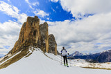 Mountaineer backcountry ski walking up along a snowy ridge with skis in the backpack. In background blue cloudy sky and shiny sun and Tre Cime, Drei Zinnen in South Tirol, Italy.   - 180955709