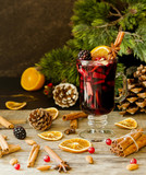 glass of hot mulled wine for the new year with ingredients for cooking, nuts and Christmas decorations - 180961541