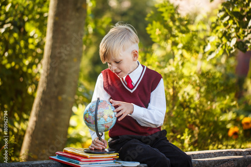 Fototapeta Adorable schoolboy with books and globe on outdoors. Education for kids. Back to school concept.