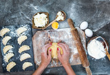 Female hands kneading raw dough on wooden board. Flowered dark table with varenyky, eggs and rolling pin. Top view, view from above.