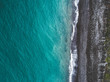 Aerial view of sea shoreline and dark pebble beach. View from above.