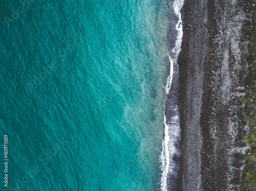Fotobehang Grijs Aerial view of sea shoreline and dark pebble beach. View from above.
