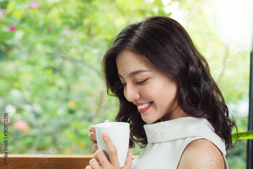 Poster Portrait of happy young business woman with mug in hands drinking coffee