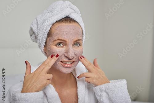 Attraktive Frau trägt Anti-Aging Gesichtsmaske auf