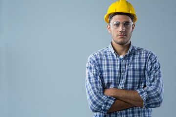 Male architect standing with arms crossed against white