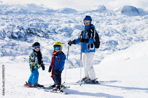 Father and two boys, skiing on a sunny day on a mountain summit in Austria resor Poster