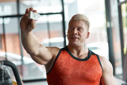 Sticker Waist up of a strong bodybuilder making selfies