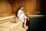 Beautiful woman sitting in finnish sauna