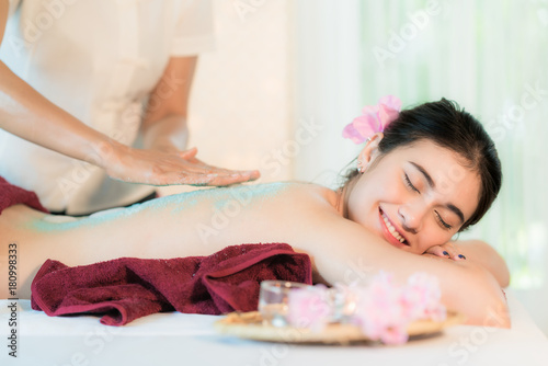 In de dag Spa Young Asian woman receiving salt massage in spa salon, Hand putting salt scrub on female back, Spa concept