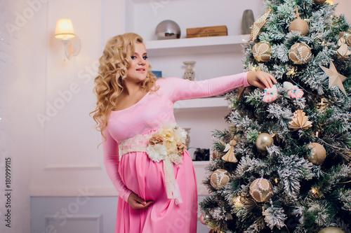 pregnant blond girl in pink dress studio