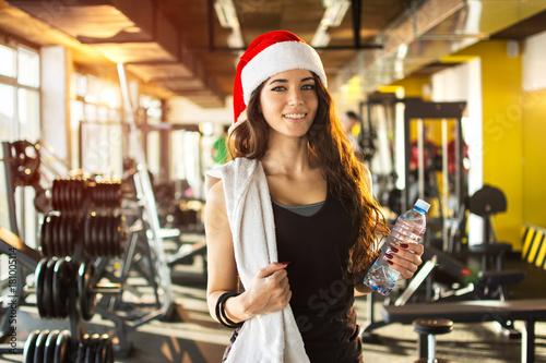 Poster Young woman with red Santa hat, towel and water bottle in gym. Snow effect on photo.