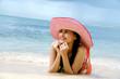 Beautiful woman wearing a hat lying on the beach