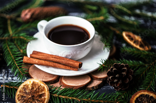 A cup of coffee with cinnamon on dark wooden background. A cup of coffee in christmas decorations