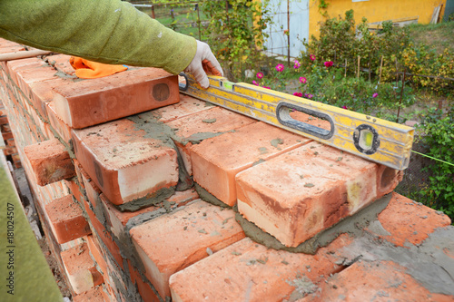 Papiers peints Brick wall Bricklayer Using a Spirit Level to Check New Red Brick Wall Outdoor. Bricklaying Basics Masonry Techniques.
