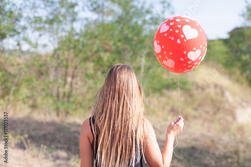 behind view of young woman with balloon Poster